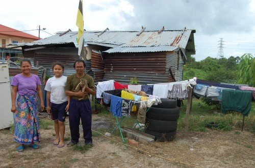 Reduan Abdullah and family standing beside the dilapidated hut